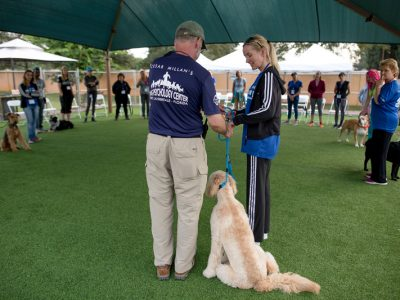 A trainer helping a pet owner to see the proper way to hold the leash